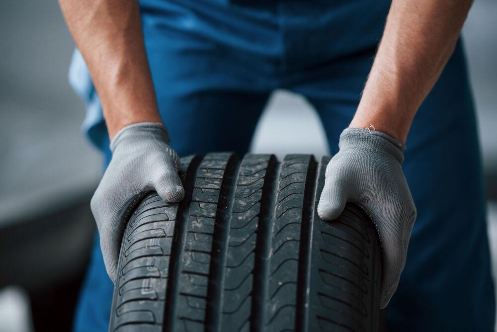 bilmekaniker står med däck i händerna